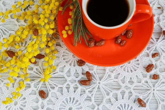 Kop en schotel zijn versierd met een mimosa en snoepjes op een mooi gehaakt tafelkleed
