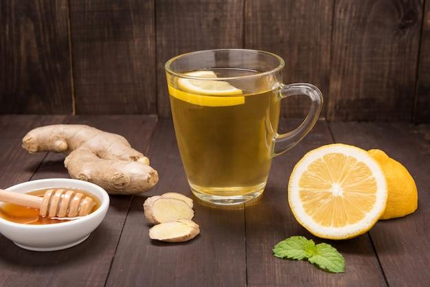 Kop gemberthee met citroen en honing op houten achtergrond