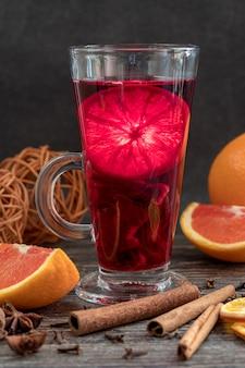 Kop hete hibiscusthee met sinaasappelen en kaneel op houten lijst