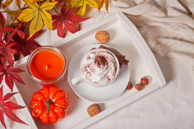 Kop hete romige cacao met schuim op het witte dienblad met de herfstbladeren en pompoenen op de achtergrond