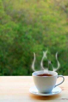 Kop hete thee met stijgende stoom op wazig groen gebladerte op de achtergrond
