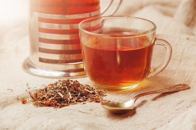 Kop hete zwarte thee, droge theebladen op een lichte jute