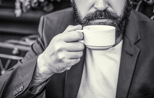 Kop koffie. cappuccino en zwarte espresso koffiekopje. koffie drinken. bebaarde man, handen met een kopje warme koffie. koffie tijd. zwart en wit.