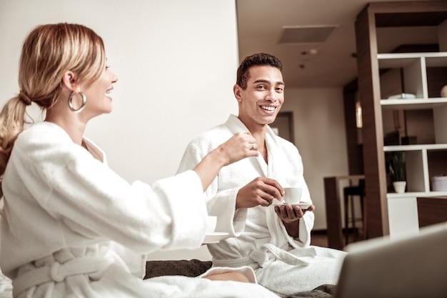Kop koffie. donkerharige vriendje bedrijf kopje koffie ontbijten op bed met zijn vrouw