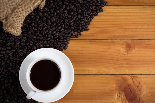 Kop koffie en koffiebonen in een zak op houten achtergrond.