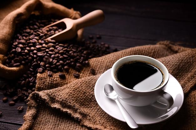 Kop koffie en koffiebonen in jutezak op oude houten achtergrond