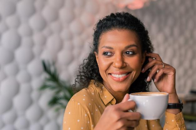 Kop koffie. portret van mooie donkerharige krullende vrouw die gele blouse draagt die van haar kop van koffie geniet