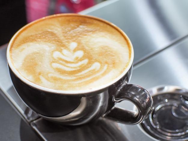 Kop latte of cappuccino met latte kunst.