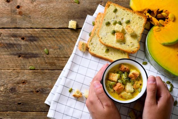 Kop met de soep van de wortelroom in meisjeshanden met zaden, crackers op houten rusti, exemplaarruimte