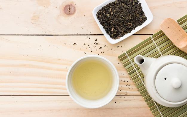 Kop met groene thee en theepot op houten tafel achtergrond