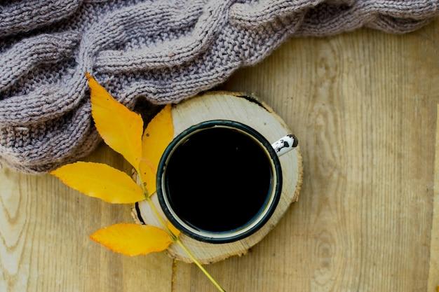 Kop met koffie op een houten standaard geel blad herfst en textiel