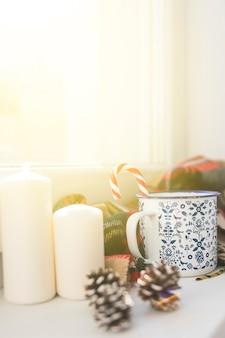 Kop met suikergoedriet dichtbij winkelhaken en kaarsen