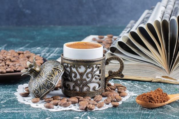 Kop schuimende koffie, plaat van koffiebonen en boek over marmeren lijst.