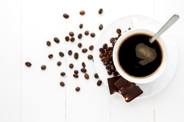 Kop sterke koffie op een witte houten oppervlakte met korrels en chocolade