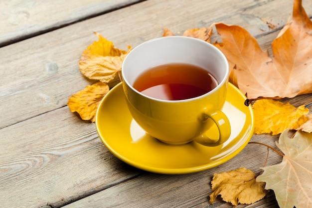 Kop thee en de herfstbladeren op de lijst