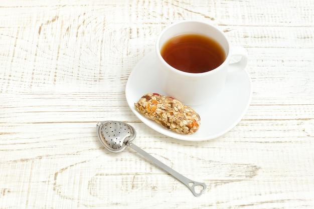 Kop thee en een reep muesli. witte houten tafel