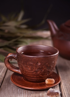 Kop thee en suiker met theepot op de achtergrond