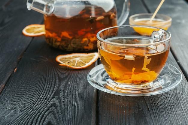Kop thee en theebladen op houten lijst