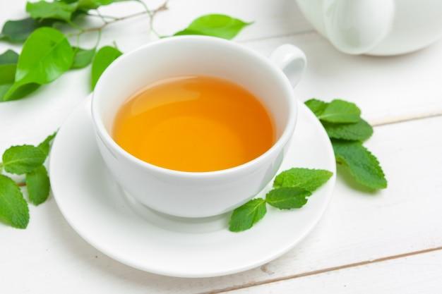 Kop thee en theebladen op witte houten lijst. detailopname.