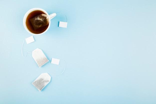 Kop thee en theezakjes op blauwe achtergrond.