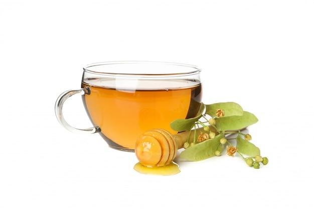 Kop thee, houten dipper met honing en linde die op wit wordt geïsoleerd