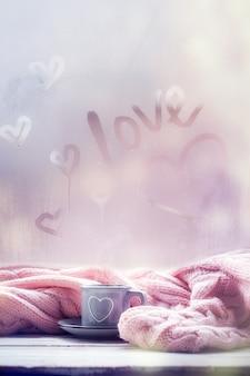 Kop thee, koffie, chocolade en roze plaid op mistig venster met liefdetekst. liefdesstemming. hygge concept.