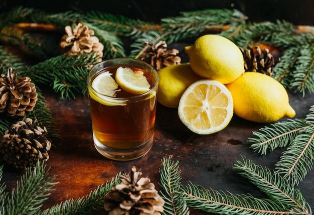 Kop thee met de citroenen van het citroenfruit met spartakken voor een rustieke achtergrond. kerstvakantie