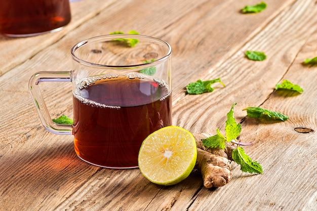 Kop thee met gember, citroen en munt op houten lijst
