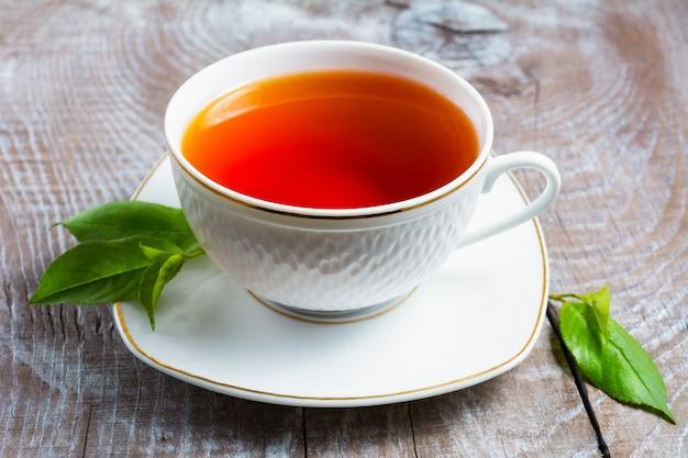 Kop thee met groene bladeren op rustieke houten lijst