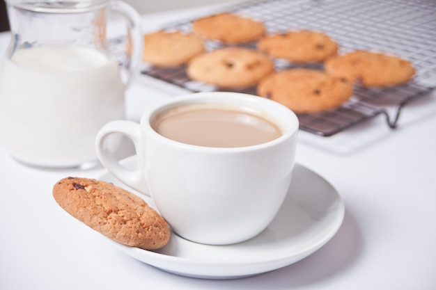 Kop thee met melk, eigengemaakte koekjes op het wit