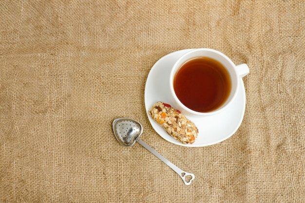 Kop thee, reep muesli en theezeef op zak. bovenaanzicht