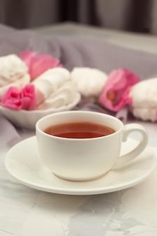 Kop thee, snoepjes en roze bloemen