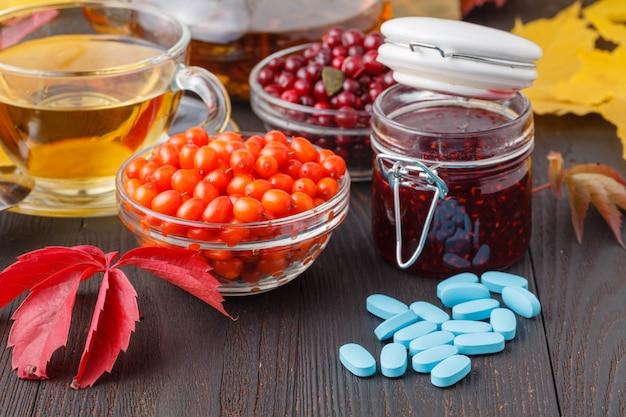 Kop van bessenthee in plaats van pillenconcept aardgeneeskunde