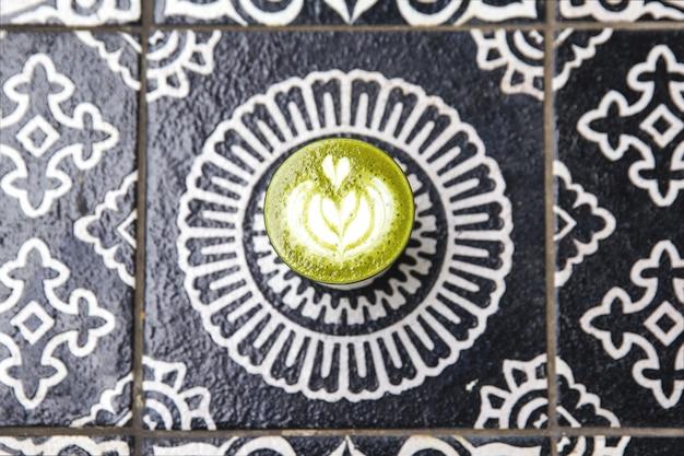 Kop van de hete koffie van matchacuccucino op kunst achtergrondvloer