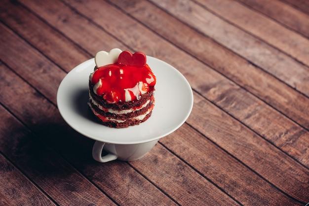 Kop van thee rode cake op een het dessert houten achtergrond van schotelsnoepjes
