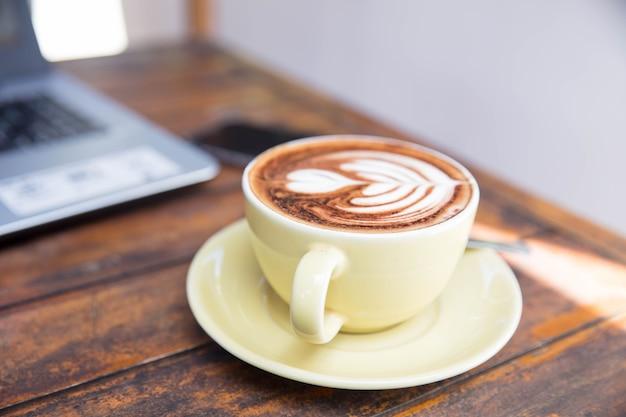 Kop van twee hete cappucino's zijn de houten tafel. hart is een kunst op één latte