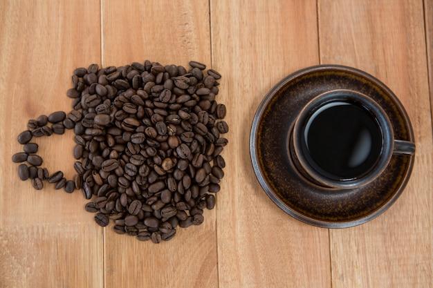 Kop van zwarte koffie en koffiebonen die vorm van kop vormen