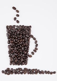 Kop van zwarte koffievorm die van bonen op witte achtergrond wordt gecreeerd