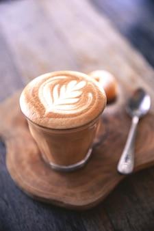 Kop warme cappucino is op houten tafel achtergrond het is latte art op de top