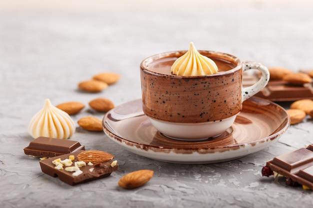 Kop warme chocolademelk en stukjes melkchocolade met amandelen op een grijze betonnen ondergrond