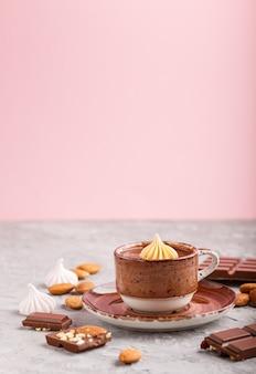 Kop warme chocolademelk en stukjes melkchocolade met amandelen op grijs en roze. zijaanzicht, selectieve aandacht.
