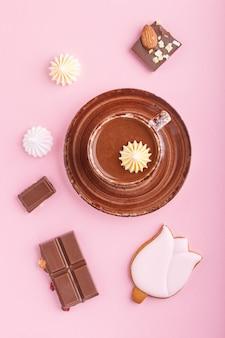 Kop warme chocolademelk en stukjes melkchocolade met amandelen op roze. bovenaanzicht.