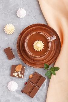 Kop warme chocolademelk en stukjes melkchocolade met amandelen