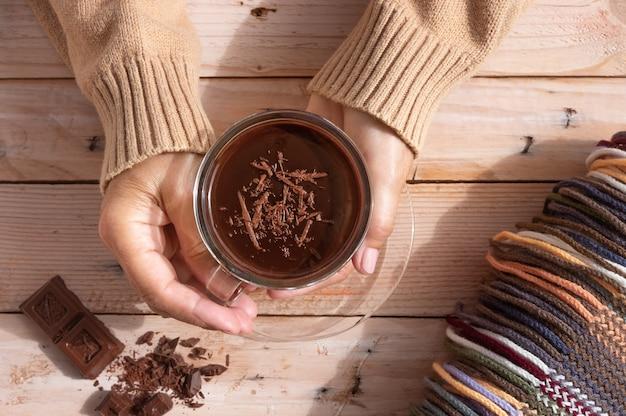 Kop warme chocolademelk in handen van de vrouw en stukjes chocola op houten rustieke tafel