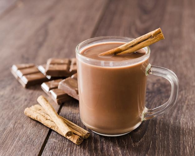 Kop warme chocolademelk met kaneelstokjes