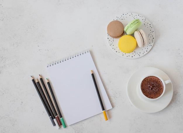 Kop warme chocolademelk met macaron, notitieboekje en potloden