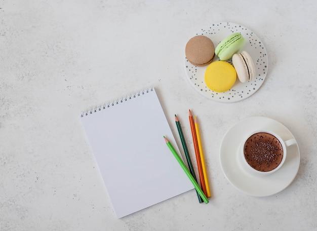 Kop warme chocolademelk met macaroon notebook en potloden