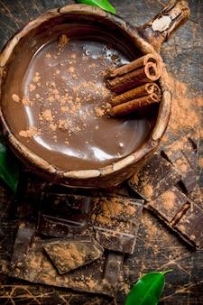 Kop warme chocolademelk met pijpjes kaneel. op een houten achtergrond.
