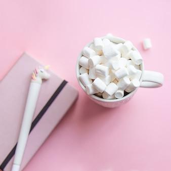 Kop warme chocolademelk of chocolade met marshmallow en notitieboekje met eenhoorn op roze.
