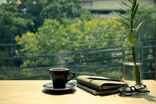 Kop warme koffie, boek, bril en plant op houten tafel.